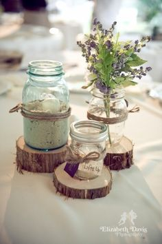 wooden blocks centrepieces , mixed with the flowers, bottles , jars with pearls and candles