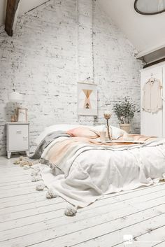 Beautiful light-grey bedroom with hints of pink and darker grey. Even the brick wall is a very light shade of grey.
