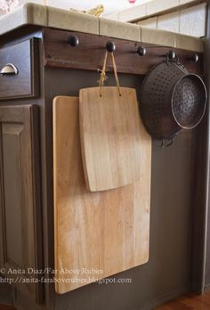 Rather than use space in her cabinets, blogger Anita Diaz added a piece of reclaimed wood to her kitchen island in order to hang cutting boards, pots, and pans.