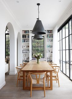 Modern dining space with floor to ceiling windows, a wall of books, a large rectangular dining room table, and wishbone chairs