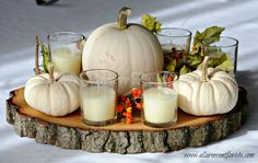 Fall wedding centerpiece with white pumpkins, candles and berries on a wood slab