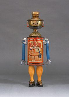 ROSETTA est une sculpture unique robot. Cette sculpture art métal fantaisiste est créée à partir des objets trouvés qui comprend une boîte de conserve, jouet bowling pins, pièces de lampe à l'huile, partie porte bougie, bijoux, bijoux perles, pièces de montres, pièces de jeu en bois, dominos, couvercle en métal, écrous et fer à cheval de pinces. Rosetta n'est pas un jouet ni elle est fonctionnel, sauf aux vous faire sourire ou rire!  -TAILLE: 13.5 haut par 5,25 de large par 2.75 de…