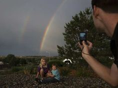 Siblings Alanna Jochim (L), 8, and Jared Jochim, 4, of Houston, Texas, pose for their father in front of a double rainbow after a heavy rain fall in Colorado Springs, Colorado July 3, 2012.