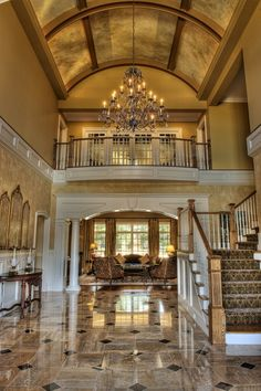 LOVE this entry way, despite my wanting a grand staircase right down the center of the room; however, I do like how - by placing the stairs on the side - the room is commanding and a person can truly enjoy the beauty of the architecture and feel welcome into the entire home.