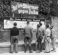 "The unceasing anti-Semitism of Der Stürmer newspaper run by radical anti-Semite Julius Streicher. Under a sign saying ""With the Stürmer against the Jews"" is a page display beneath the Nazi slogan ""The Jews are our misfortune."""