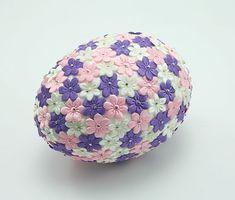 Przypinanie szpilkami kwiatków do styropianowego jajka