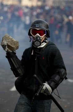 A protestor holds a rock during clashes with police outside the steel security barriers around the National Congress, where the swearing in of new Mexican President Enrique Pena Nieto is taking place in Mexico City, Saturday Dec. 1, 2012