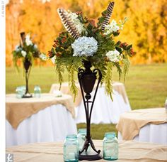Tall vases filled with white flowers and accented with turkey feathers were set up at each reception table, with antique mason jars and tealights surrounding the centerpieces.