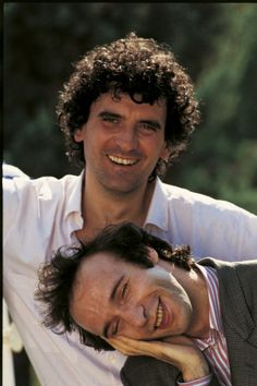 Portrait of Italian actors and directors Roberto Benigni and Massimo Troisi smiling. 1984 MONDADORI PORTFOLIO