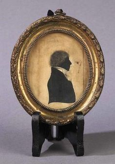 English Ink-on-Paper Silhouette of a gentleman in a stock collar in the original gilt pressed-metal and wood oval frame, ca. Late 18th Century
