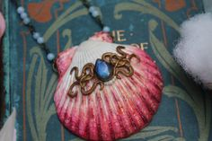 A beautiful handmade polymer clay sea shell necklace from By Amillia, featuring a deep blue labradorite cabochon and filigree detail in an antique bronze tone. The necklace chain is made up of little aquamarine bubbles ✧ To see more visit www.byamillia.com or follow me on Instagram @byamillia ✶ #seashell #mermaid #mermaidjewelry #shelljewelry #aquamarinenecklace #oceanart #mermaidart