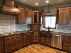 White subway tile, dark grout with stained hickory cabinets, copper sink and…