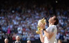 Andy Murray raising the iconic Wimbledon trophy to the sky after his 2013 victory. A look of pure relief and genuine emotion across his face.