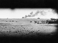 In this image provided by the U.S. Marine Corps, these U.S. Marine motion pictures, taken through the front slot of a Marine tank on Iwo Jima on March 3, 1945, show Marines advancing behind an armored vehicle as another American vehicle burns in the background.
