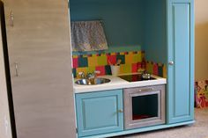 DIY play kitchen made from a repurposed TV entertainment center