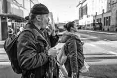 A man standing at the traffic light with an empty food tray in his hand. Street Pictures, Man Standing, Couple Photos, Couple Pics
