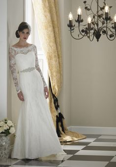 Slim fish tail soft delicate lace gown with lace and with a silk underlay on the shoulder and full length fitted sleeve. Fastening on the back and cuff of sleeve with covered button and finished with a high quality crystal belt in silk tied at the waist