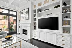 Chic white living room features a built in flat panel television fixed above white cabinets adorning brass hardware and framed by white cabinets located beneath custom lit glass front display cabinets.