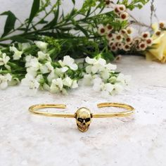 Skull statement bangle in gold... Shop now by clicking on website - Inspired by the romance of nature and memento mori... the Eternal skull palm cuff bangle   Au Revoir Les Filles
