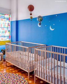 Quarto infantil com parede azul, berço de madeira clara e tapete colorido.