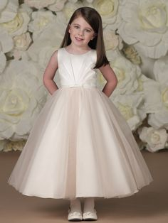 Sleeveless satin and tulle tea-length A-line dress with jewel neckline, center sunburst pleated satin bodice features a thin waistband with center front bow, satin covered buttons down back bodice are finished with large fixed center bow, double layered tulle overlay skirt.