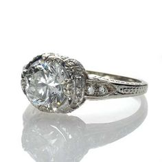Replica Art Deco Engagement Ring    Set with an Round Brilliant cut diamond weighing 1.71 cts and assessed by the GIA as L color and SI1 clarity,this stunning 14k white gold ring is encrusted with 32 round bead set diamonds with additional hand engraved detailing. This beauty is an exact replica of an Art Deco engagement ring from the 1920s.