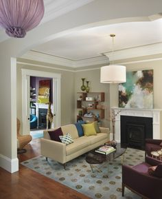 a version of what my living room could be: eclectic tan  purple living room design with tan walls paint color, Jonathan Adler Meurice pendant, tan modern sofa, blue  brown medallions rug, purple velvet chairs, brass oval coffee table, abtract art, bookshelf and purple lime green pillows.