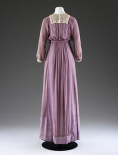 Dress, Mascotte, 1912, London.  In  V&A: CIRC.643-1964  Owned by Miss Heather Firbank  Silk chiffon over silk, grosgrain, lace, boned, embroidered. This dress shows the new slim line and tubular skirt of the 1910s. Its almost austere appearance is made more feminine with the addition of a double line of self fabric decorative buttons down the front and at the cuffs and a purple cord sash which ties around the waist and falls at one side.