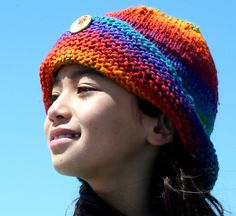 This is a super easy cloche style hat that's made to show off your favorite heavy yarns. It requires approximately 150 yards of heavy worsted weight or Aran yarn to make a large hat, a pretty matching decorative button to hold up the side brim, and 2 circular needles or 5 straights to knit in the round. The simple construction lets your yarn be the star; it works well with long-color shifting yarns, multi-colored yarns and handspuns. It makes a good instant gratification knit and is mindless…