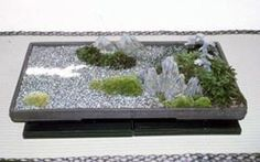 a miniature landscape in a ceramic pot; stones representing mountains and mosses forested lands or islands, sand seawater; work by late T. Oishi