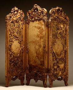 The 3 tiered screen has central arched panel asymmetrically carved with pierced acanthus and C-scrolls, framing a scene of an amorous 18th century couple by a tree, with deer in a landscape to the reverse, flanked by similar asymmetrically-carved panels decorated with floral swags and foliate scrolls, centering cartouches depicting frolicking putti, on slightly cabriole legs ending in scroll toes.