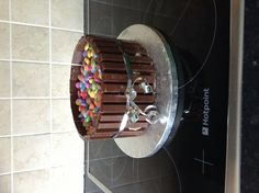 Plain cake with jam and frosting inside with kit Kat's around the outside and smarties in the middle