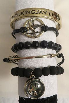 "Up for sale is the official Hunger Games ""Arm Candy Set"" pictured. You'll be getting a set of 5 bracelets. Ages 14+ Wear them alone or stacked. This is an official Hunger Games product. Jewelry is new"