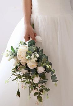 Product Details - A romantically rustic silk flower arrangement for the modern bride or bridal party - Consists of luscious white ranunculus, garden roses, silver dollar eucalyptus, and assorted greeneries - Wrapped with a soft white satin ribbon - The bouquet measures approximately 17