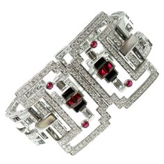 CARTIER. This fabulous bracelet from Le Baiser Du Dragon collection fuses inspiration from Chinese culture and Art Deco style in a magnificent design made of 18k white gold and set with faceted and cabochon multi-shaped black onyx and ruby stones as well as sparkling round diamonds. Circa 2003.