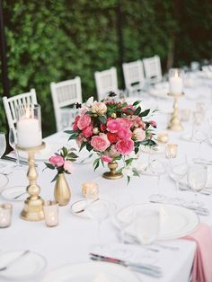 white and blush pink wedding inspiration | elegant bright pink centrepieces and raised gold pillar candles | gold votives on white table cloths | Photography: Lane Dittoe - lanedittoe.com