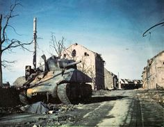 A destroyed Sherman tank. *Note the dead crew member cover in front.