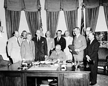 Eleven men in suits stand around a large desk at which another man is signing a document.