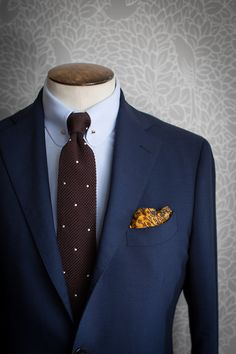 Navy jacket, light blue shirt with pin collar, brown knit tie with white pin dots