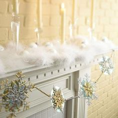 Nestled in fluffy ostrich feather boas, glass candlesticks with creamy white candles seem to float on clouds. A garland of gold and silver beads and layered snowflake ornaments adds an elegant touch.