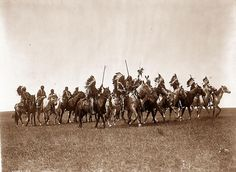 You are viewing an original photograph of Sioux Warriors on Horseback. The photo is by Curtis, and was taken in 1907. The photograph shows Brule Indians, many wearing war bonnets, on horseback.