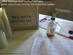At a public school foundation auction in a rural community, the silent auction space was intermixed with tables from wineries offering samples, and vendors like this #WildRootsApothecary, with fun drinks.  Click thru to read more about this event. #SchoolAuctionIdeas