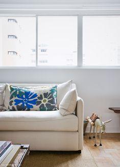 Sofá bege, almofada com estampa tropical e peça de arte popular brasileira.