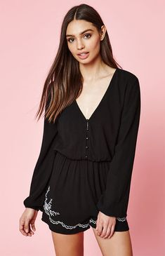 Jump-start the spring season in this boho-inspired romper by Kendall & Kylie. The Embroidered Long Sleeve Romper has a flowy fit and features a deep V-neckline, a button front, and embroidered floral detailing along the hem.   	Lined, solid color romper 	Embroidered detailing on hem 	Deep V-neckline 	Long sleeves with elasticized cuffs 	Button front 	Flowy fit 	Model is wearing size small 	Model's measurements: Height: 5'8.5'' Bust: 32'&a...