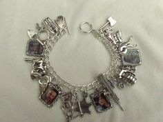 THE WALKING DEAD LOADED PICTURE CHARMS BRACELET, MADE BY MYSELF, WITH 4 TIBETAN PICTURE FRAME CHARMS, PICTURES ARE RICK, DARYL, CARL AND MICHONNE, ALL SEALED WITH RESIN, BRACELET IS SILVER-PLATED CHAIN AND 7.5 INS LONG WITH TOGGLE FASTENER, MOST OF THE CHARMS ARE TIBETAN SILVER AND ARE:  AXE  TANK  BINOCULARS  WALKER/ZOMBIE  BABY FEET  LANTERN  GRENADE  MOTORBIKE  MACHINE GUN  SHERIFF BADGE   CROSSBOW  TRUCK  HANDCUFFS  COWBOY HAT  HORSE  PISTOL  SPADE  KEYS  COFFIN  HAND