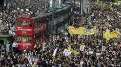 Trams sit stranded as thousands of people block the streets in a huge protest march against a controversial anti-subversion law known as Article 23 in Hong Kong, 1 July 2003