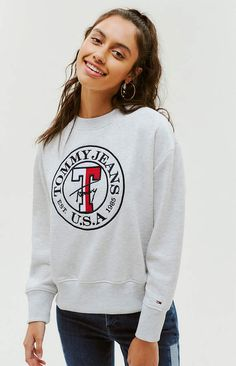 Layer up for fall with the Logo Sweatshirt by Tommy Jeans. This classic sweatshirt features a soft fleece lining to keep you warm and cozy and is finished with long sleeves, crew neckline, embroidered logo at the chest, and ribbed cuffs and band. Tommy Jeans Sweatshirt, Graphic Sweatshirt, Hoodie, Teen Fashion Outfits, All About Fashion, Tommy Hilfiger, Autumn Fashion, Sweatshirts, How To Wear