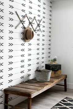 Rustic and modern mudroom with graphic black and white arrow wallpaper, a reclaimed wood bench, metal bucket as a catchall for gloves and hats, glass terrarium for a bit of green, and an expandable hat rack on the wall for easy and accessible storage.