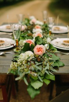 Brides.com: Unique Centerpiece Idea: Fresh Flower Runners. This simple, rustic floral runner combines blush garden roses, white ranunculus, and tons of bright leaves.