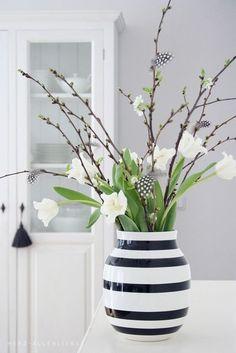 Eine zurückhaltende, aber sehr schöne Zusammenstellung von Blumen, Zweigen, Federn und einer schlichten Vase.